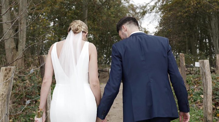 Brautpaar geht einen Waldweg entlang