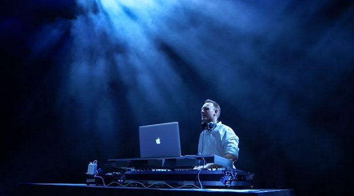 DJ mit Pult auf großer Bühne in blauem Licht