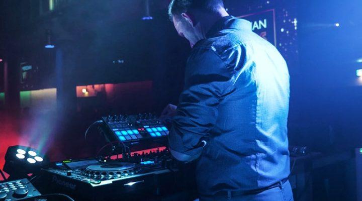 DJ steht am Mischpult im Edelfettwerk, blaues Licht strahl ihn an