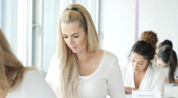 Frau weiß gekleidet sitzt in einem Seminar und macht Notizen