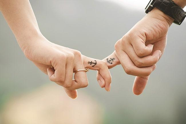 Hände eines Ehepaares halten sich an den Zeigefingern fest. Beide Finger haben ein Ankertattoo.
