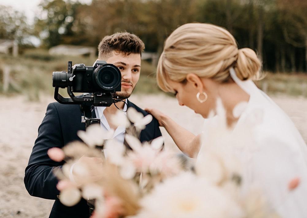Hochzeitsvideograf mit Braut am Strand - Braut stützt sich ab