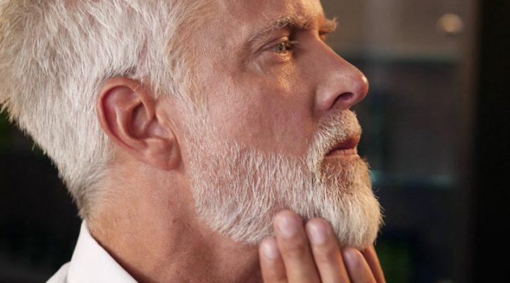 Männliches Model weiße Haar fährt mit der Hand durch seinen Bart beim Barbier