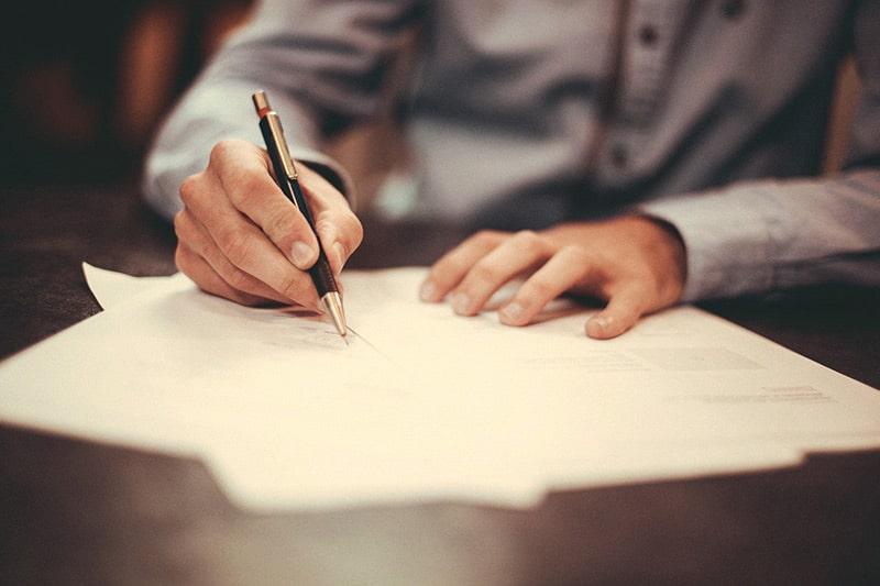 Mann hält einen Stift und unterschreibt Verträge auf dem Tisch