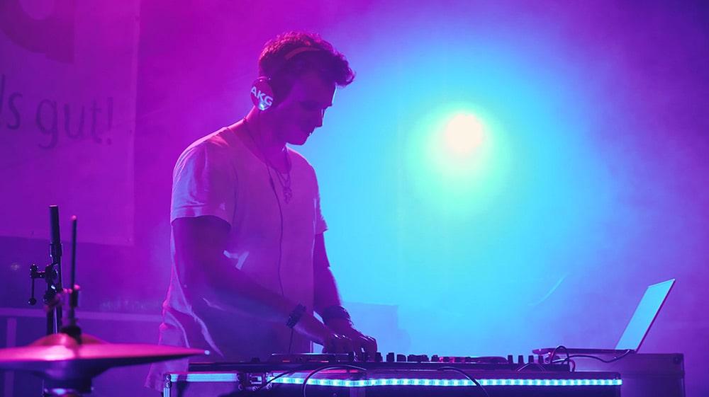 DJ steht vor einem Pult auf der Bühne bei lila-blauem Licht