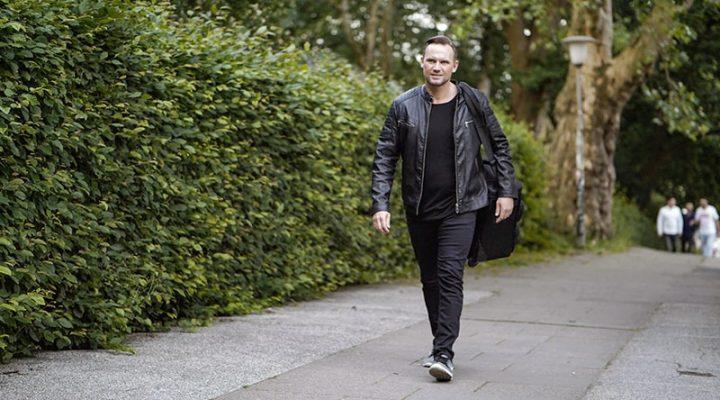 Mann geht einen Weg vor einer Hecke entlang