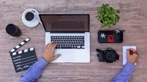 Videograf sitzt am Schreibtisch und macht Notizen