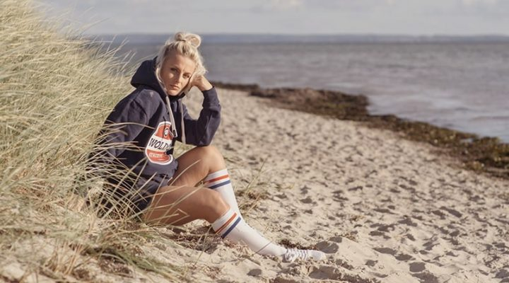 Frau sitzt am Strand mit Woldo Athletic Kleidung und blickt zum Betrachter